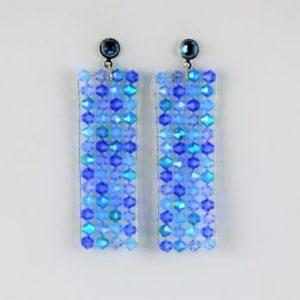 Boucles d'oreilles en perles SWAROVSKI® ELEMENTS bleues, montées sur un cadre en fil d'argent massif 925 et tissées par un fil nylon transparent.